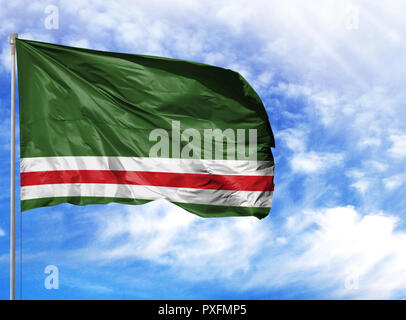 National flag of Chechen Republic of Ichkeria on a flagpole in front of blue sky. - Stock Photo