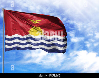 National flag of Kiribati on a flagpole in front of blue sky. - Stock Photo