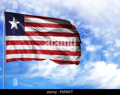 National flag of Liberia on a flagpole in front of blue sky. - Stock Photo