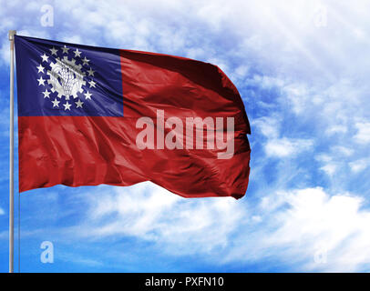 National flag of Myanmar-Burma on a flagpole in front of blue sky. - Stock Photo