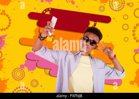 Cool mulatto teenager wearing dark sunglasses making selfie using his smartphone - Stock Photo