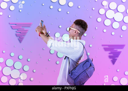 Cool schoolboy wearing striped shirt and blue backpack making selfie in sunglasses - Stock Photo
