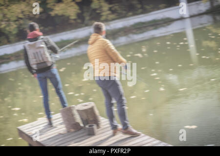 Two fishermen with fishing rods catching fish, spinnings standing on the bridge, pier, blured background. Active rest in autumn, hobby, countryside relaks - Stock Photo