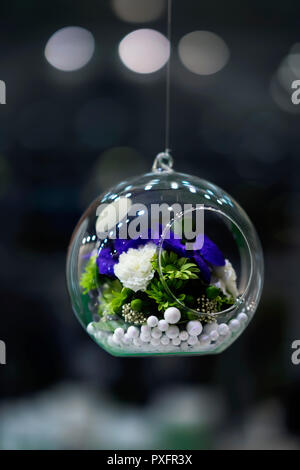 Hanging glass ball, bubble with colorful flowers inside, dark background, bokeh, decoration, stylish floristry - Stock Photo