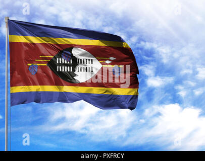 National flag of Swaziland on a flagpole in front of blue sky. - Stock Photo