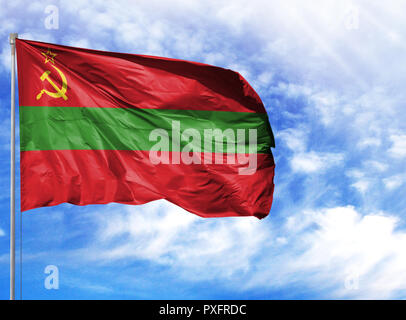 National flag of Transnistria on a flagpole in front of blue sky. - Stock Photo