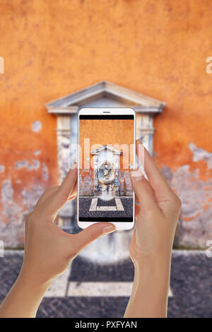 A tourist is taking a photo of small drinking fountain with sculpture and stone decor in shabby painted wall, Rome on a mobile phone - Stock Photo