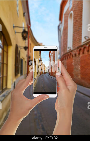 A tourist is taking a photo of empty street in old town of capital of Lithuania - Vilnius on a mobile phone - Stock Photo