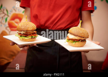 Hot appetizing hamburger on a plate in the hands of the waiter. - Stock Photo