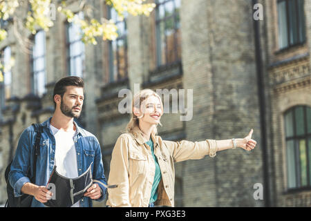 portrait of young tourists with map hitchhiking on street - Stock Photo