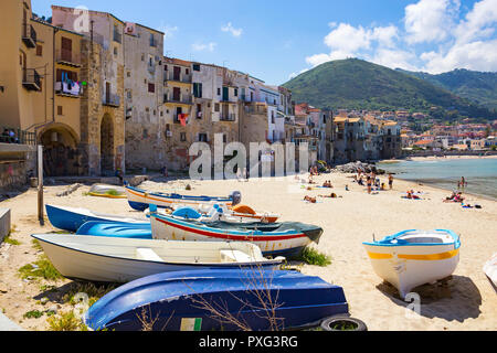 CEFALU, ITALY - MAY 12, 2018: People sunbathing on beautiful small beach in Cefalu old town on Mediterranean sea, Sicily - Stock Photo