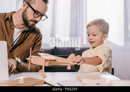 father using laptop while smiling son playing with wooden plane model - Stock Photo