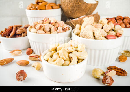 Various types of nuts - walnuts, pecans, peanuts, hazelnuts, coconut, almonds, cashews, in bowls, on a white marble table top view - Stock Photo