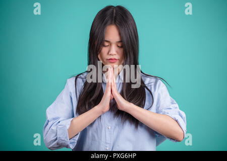 Asian young woman praying on blue studio background. - Stock Photo
