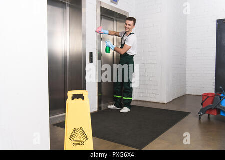 handsome young janitor cleaning elevator and smiling at camera - Stock Photo