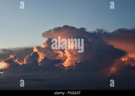 Cumulonimbus cloud formations on tropical sky with horizon is turning yellow at sunset , Nimbus moving , Purple and orange color clouds hunk at night - Stock Photo