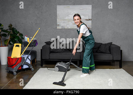 happy young female cleaning company worker using vacuum cleaner and smiling at camera - Stock Photo