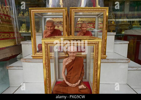Fibre glass miniatures of revered Thai monks - or Luang Pu - in gold-rimmed glass cases, on sale in Bamrung Muang Rd., Bangkok, Thailand - Stock Photo
