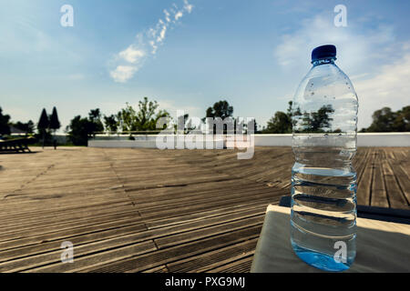 Half empty plastic bottle of mineral water on the wooden pallet on the hotel terrace - Stock Photo