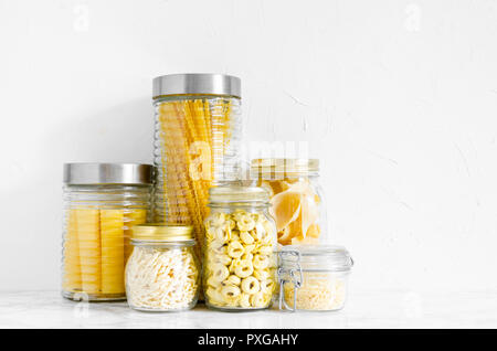 Variety of types and shapes of Italian pasta in glass jars on white background. Italian cuisine food storage concept. Copy space. - Stock Photo