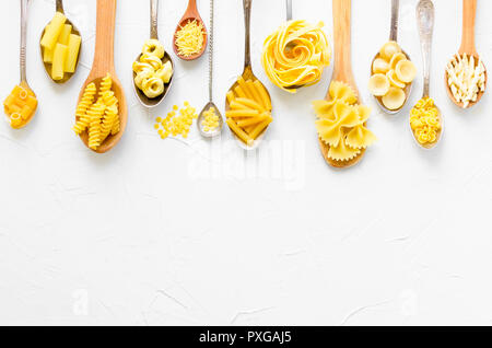 Variety of types and shapes of Italian pasta in wooden spoons on white background from above. Italian cuisine food concept and menu design. Dry pasta  - Stock Photo