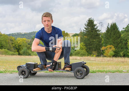 Young caucasian man drives electrical mountainboard on road in nature - Stock Photo