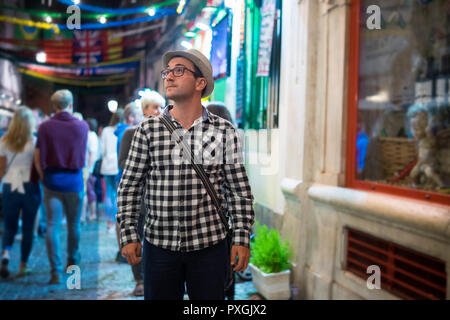 Young serious man looking right on colorful street at night - Stock Photo