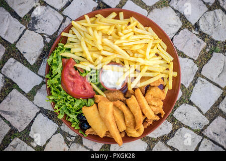 Famous choco frito of Setubal. Fried squid and octopus served with french fries and salad. - Stock Photo
