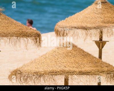Summer symbol - straw umbrellas on sunny beach of Portugal - Stock Photo