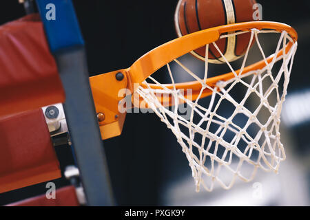 Basketball scoring basket at a sports arena. Scoring the winning points at a basketball game. The orange basketball ball flies through the basket - Stock Photo