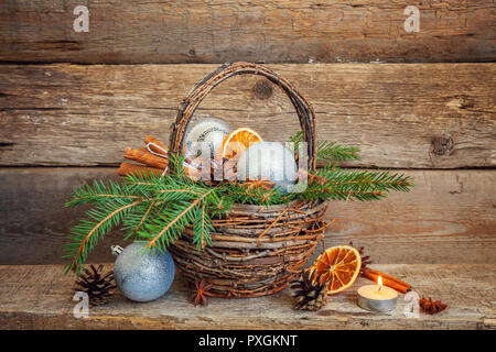 Christmas New Year composition winter objects fir branch basket pine cones balls orange slices cinnamon sticks on old shabby rustic wooden background. - Stock Photo