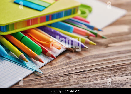 Stationery under a bright notebook on the table - Stock Photo