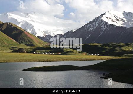 Lake Tolpur + peak Lenin ( Pamir mountains,  Kyrgyzstan). Tourist yurt camps are visible in the background. - Stock Photo