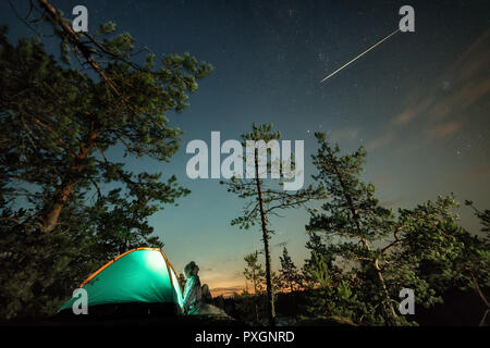 Man looking on nigh starry sky with falling star. Outdoor night scene. Long exposure, grain visible - Stock Photo