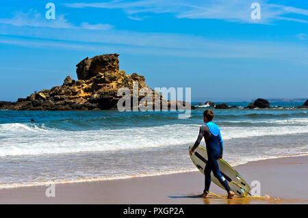 Surfer at the Praia do Castelejo beach at the Costa Vicentina coast, Vila do Bispo, Portugal - Stock Photo