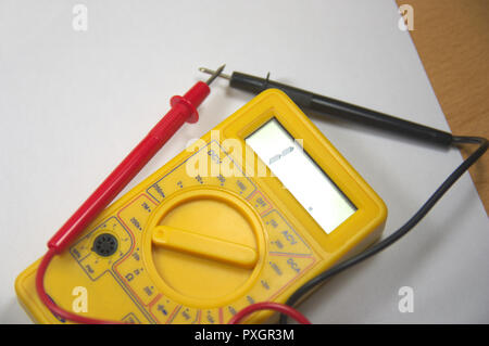 Close-up from above of a digital multimeter with its black and red test tips - Stock Photo