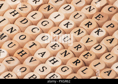 Capital wooden block letter A-Z alphabet set in wooden box isolated on wooden background - Stock Photo