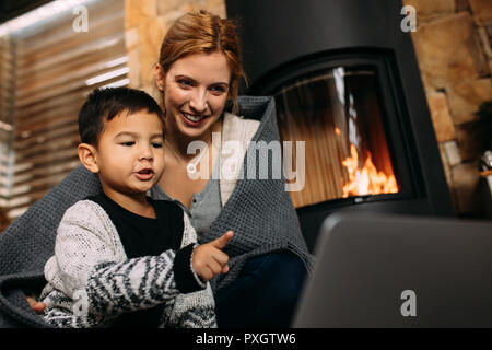 Little boy pointing at laptop while sitting with mother near fireplace at home. Mother and son looking at something interesting on laptop computer in  - Stock Photo