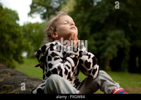 Little curly girl prays sitting on a stone fence. Rest in the village. Prayer to God. Summer holidays. - Stock Photo