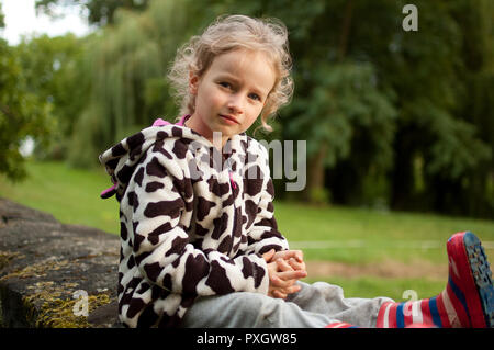 Portrait of a beautiful curly blue-eyed girl sitting on a background of green trees. Vacation in the village. Schoolgirl on vacation. - Stock Photo