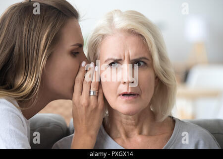 Adult daughter share secret with surprised aged mom - Stock Photo