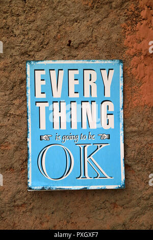 Positive quote of EVERYTHING is going to be OK on the blue plate hanging on the rough brown wall - Stock Photo
