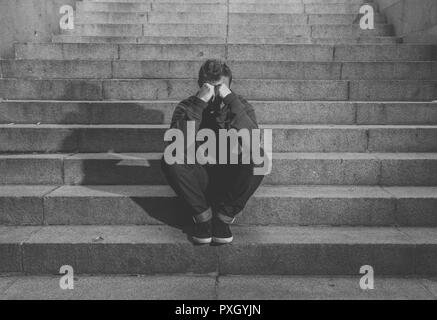 Young desperate jobless man in casual clothes abandoned lost in depression sitting on ground concrete stairs alone in grunge lighting in Emotional pai - Stock Photo