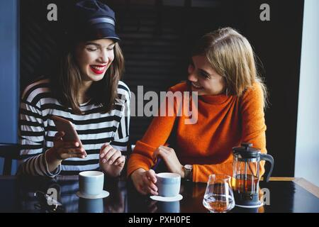 Two young women sitting in a cafe, drinking their morning coffee and surfing the net on smart phones.
