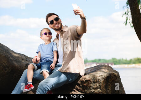 father and son taking selfie with smartphone at park - Stock Photo
