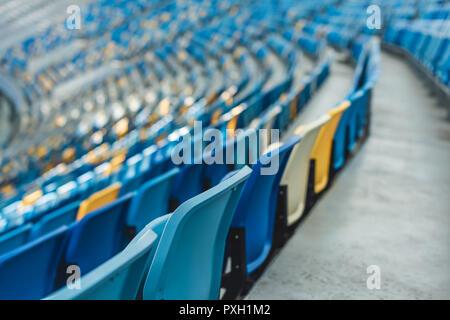empty colorful seats on tribunes of modern stadium - Stock Photo