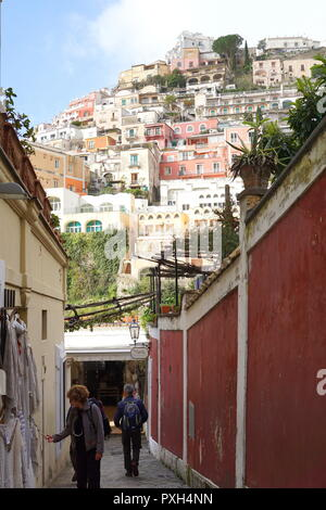Tourists walking on a narrow street with the backdrop of colorful homes  in Positano, a cliffside village on southern Italy's Amalfi Coast - Stock Photo