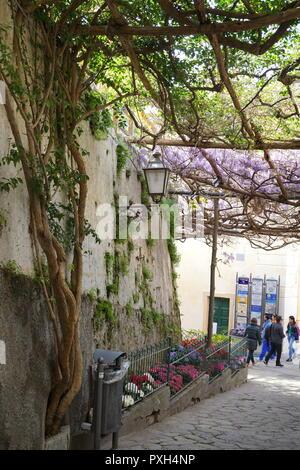 Travelers walking on the steep narrow street in Positano, a cliffside village on southern Italys Amalfi Coast - Stock Photo