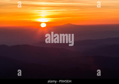 Beautiful sunset with sun coming down behind various layers of mountains - Stock Photo
