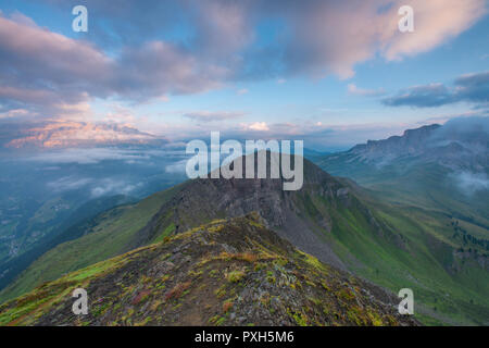 Wonderful sunrise with a view over different mountain ranges in the Italian Alps. Painted sky with low, colorful clouds. Grassy and rocky ridge.